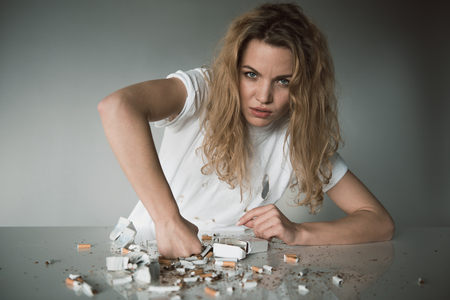 Portrait of serious female sitting at table and smashing cigarettes. Isolated on background