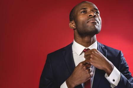 深刻なビジネス態度。エレガントな成功した若者が立って、彼のネクタイを調整しています。左側のスペースをコピーします。赤い背景で分離