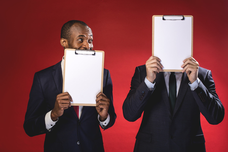 Find your partner. Cheerful pleasant young men are holding sheets of paper and hiding behind them while standing isolated on red background