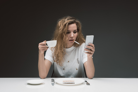 Portrait of serene girl smoking while relaxing with mobile phone and mug in hands. Plate with cigarettes and cutlery are on table. Isolated on background