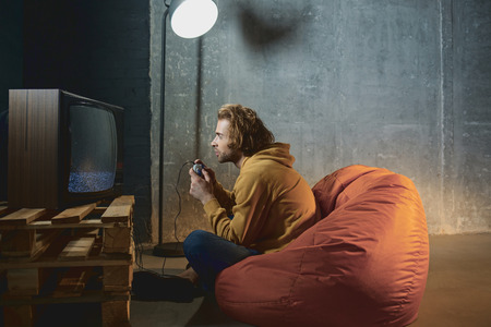 Side view engaged male typing in joystick while looking at monitor of retro television set. Rest during weekend concept
