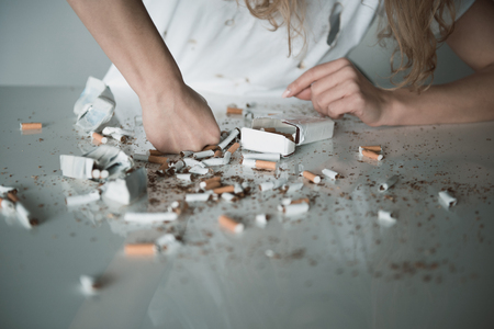 Close up of female hand smashing cigarettes, shredded cigars are scattered all over the table