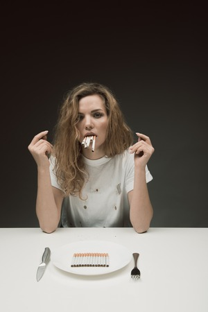 Portrait of unhappy woman relaxing at a served table and holding many cigarettes in mouth. Rollups lying in the plate. Isolated on background