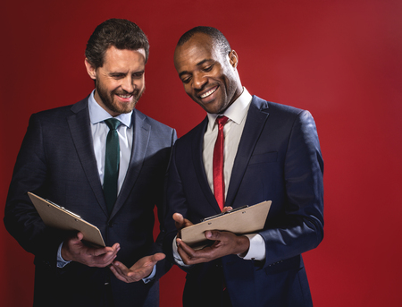 Business plan. Cheerful young elegant entrepreneurs are standing together with folders and talking with smile. Isolated on red background Stok Fotoğraf