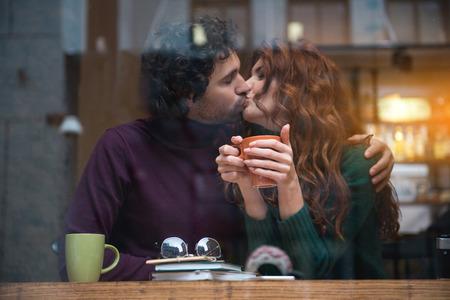 唇にロマンチックなキスを持つ陽気な若い男女。居心地の良いカフェのテーブルに座っている。