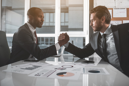 Who is stronger. Side view profile of two managers are sitting opposite each other with one elbow resting on table, clasp each others hands, and trying to force each others arm down onto the desk Stock Photo