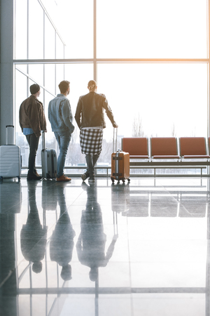 Full length men looking at window while holding luggages in airport. Inspiration and friendship concept. Copy space