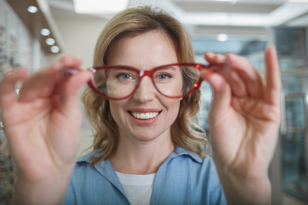 Portrait of glad woman holding eyeglasses in arms in optical store. Ophthalmology concept