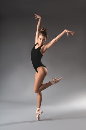 Full length portrait of slender female gymnast in black leotard standing on one leg with hands up