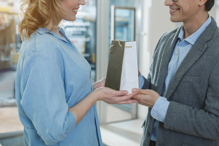 Outgoing wife and cheerful husband holding purchase in arms. Eye care concept
