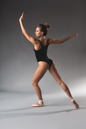 Back of slim woman in leotard standing in elegant position with calmness