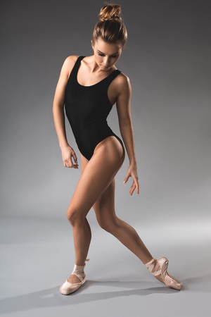 Full length of slim calm ballet dancer standing in leotard and looking down
