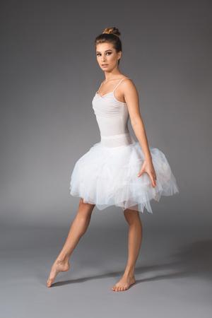Full length portrait of female dancer standing in ballet skirt and straightening one foot Stock Photo