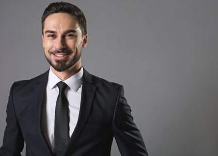 Sense of joy. Waist up portrait of bearded joyful man in business suit, he is looking at camera with felicity. Isolated on grey background and copy space in right side 写真素材