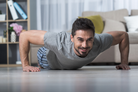 Portrait of smiling strong guy in living room doing push ups on floor 写真素材