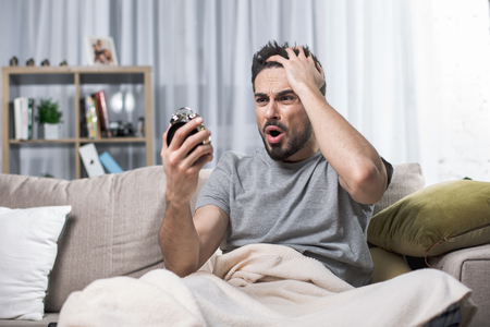Waist up portrait of stressed adult guy on couch looking at clock and holding his hand on head expressing shock