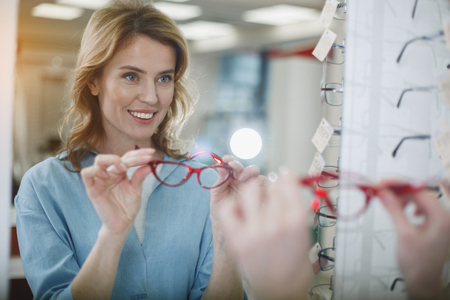 Portrait of happy woman admiring reflection in optician shop. Good vision concept Stock Photo