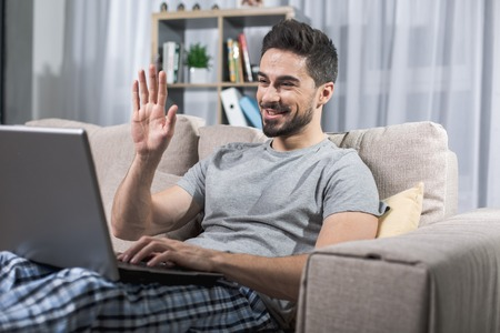 Portrait of happy attractive man on couch, he is looking at notebook screen and waving his hand cheerfully 写真素材