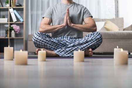Low angle of tranquil man sitting in lotus position with clasped hands. Lighted candles standing on floor