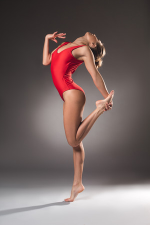 Side view of well built lady demonstrating her supple body while making gymnastic pose Stock Photo