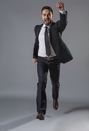 I am winner. Full length portrait of joyful smiling businessman with hand up jumping. Copy space in left side