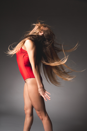 Side view of elegant girl with loose hair throwing her head back, she is wearing red maillot
