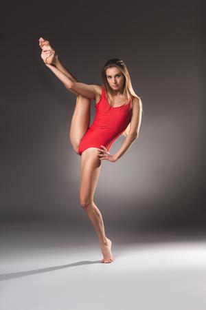 カメラを見て脚を立ち上げる穏やかな柔軟なスリムな女性のフルレングスの肖像画