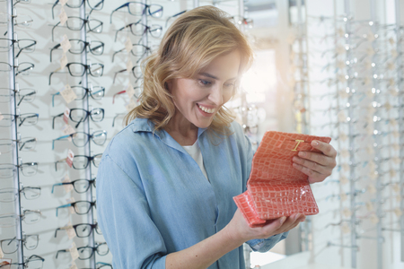 Portrait of cheerful woman looking at spectacle case. Different spectacles locating on shelves. Eye care concept Stockfoto