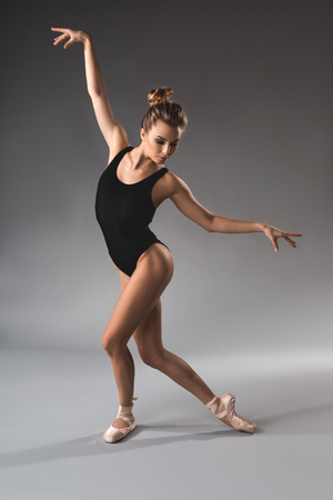 Full length of young serene girl in tricot and pointe making choreography movement