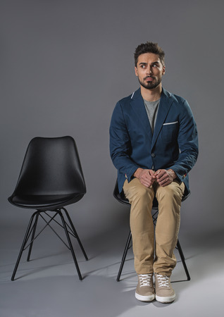 Full length portrait of nervous male is open-eyed. He is waiting for his turn on chair. Copy space in left side