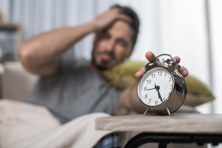 Focus on alarm clock standing on table. Man on background is turning it off Stock fotó