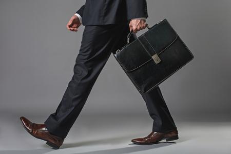Lage hoek close up van mannelijke benen. Mens die in pak met koffer loopt Stockfoto - 97245494