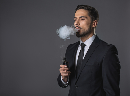 Waist up portrait of thoughtful handsome man. He is standing and smoking. Isolated on gray background. Copy space in left hand Standard-Bild