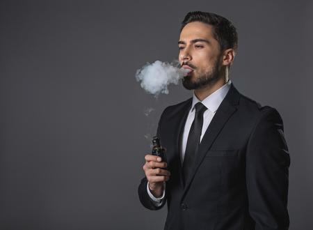 Taille portret van doordachte knappe man. Hij staat en rookt. Geïsoleerd op grijze achtergrond. Kopieer de ruimte in de linkerhand