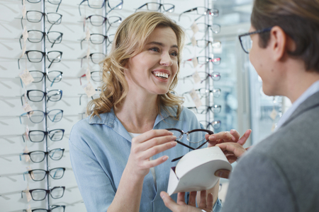 Cheerful lady keeping modern spectacles from box. She telling with man. Ophthalmology concept