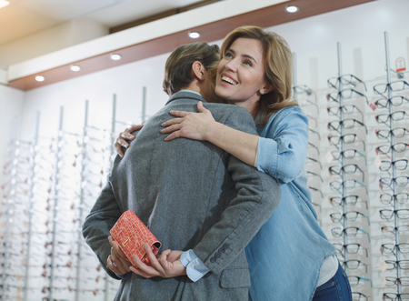 Low angle outgoing female hugging man. He turning back to camera while holding present for her. Different eyeglasses locating on shelf. Ophthalmology concept Stock Photo