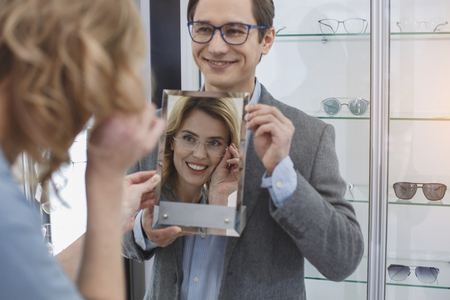 Outgoing woman looking at mirror while wearing spectacles. Buyer in optician shop concept