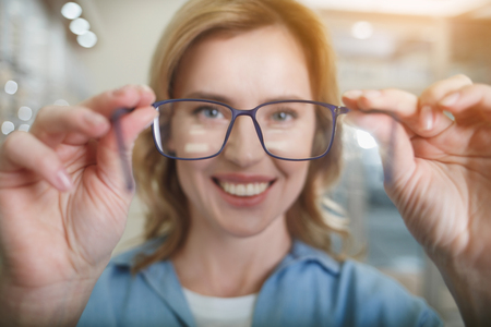 Portrait of cheerful female client hanging out glasses while looking at camera. Eye care concept