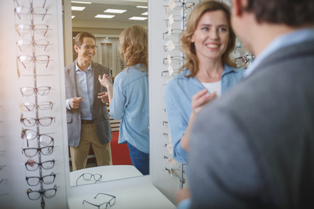 Portrait of outgoing male wearing eyeglasses while telling with female. He standing opposite mirror. Ophthalmology concept