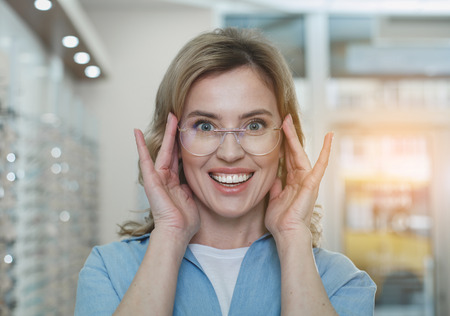Outgoing female wearing modern eyeglasses in optician store. Ophthalmology concept