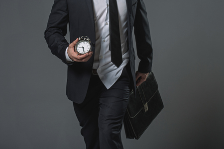 Close up of untidy tardy businessman. Shirt jerked from trousers. He carrying alarm clock and briefcase. Isolated on gray background
