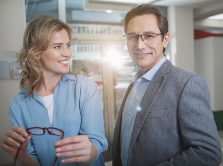 Portrait of happy woman and outgoing male situating in optician store. Female holding eyeglasses in arms. Eyesight correction concept Stock Photo