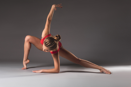 Thin young lady in red leotard doing gymnastic exercise on the floor with elegance