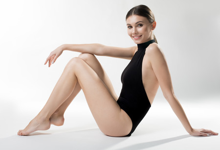 Portrait of confident girl sitting on flooring in graceful pose. She is smiling. Perfection concept Standard-Bild
