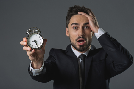 Waist up portrait of scared and discouraged man clutching head and showing time at snooze. Focus on alarm clock. Isolated on gray background