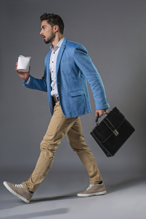 Full length of young surprised businessman is opened-mouthed and wide-eyed, holding breifcase and bearing container with fast food in hand