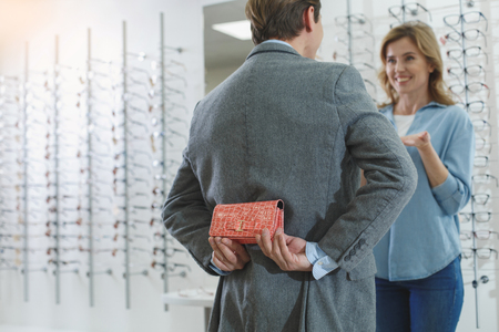 Male secreting spectacle case for smiling woman. They speaking with each other. Eyesight and gift concept Stock Photo - 97245743