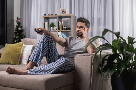 Sad young male relaxing on comfortable couch with tv remote. Big houseplant standing beside him