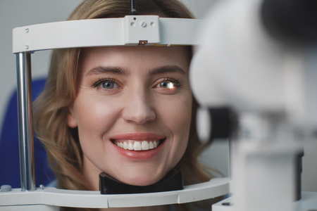 Portrait of close up beaming woman checking eyes in ophthalmological center. Eye care concept Stock Photo