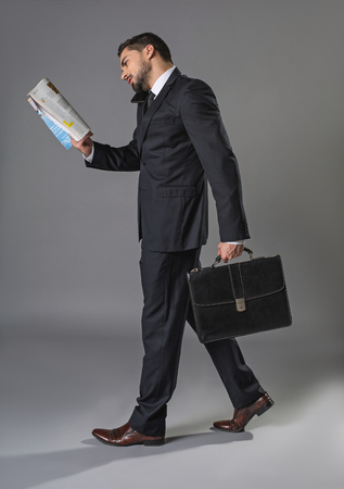 Occupied stylish man. Full length of overworked businessman going and holding cellphone with shoulder, reading magazine. Multitasking concept Banco de Imagens
